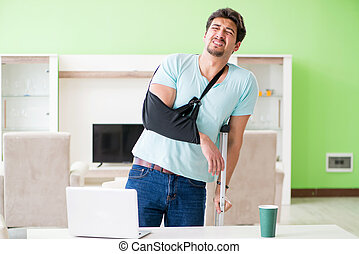 Injured man with crutches sitting at home