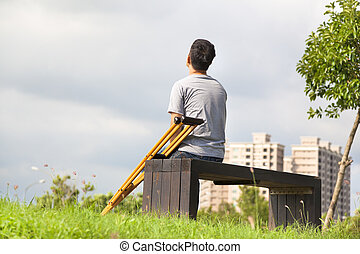 Injured Man with Crutches sitting on a bench