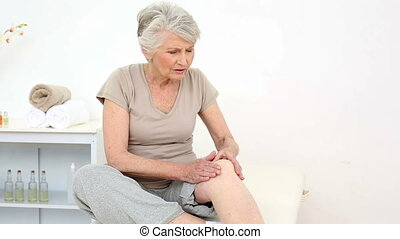 Injured patient rubbing her sore knee at the rehabilitation...