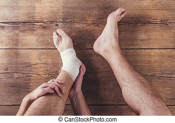 Injured runner - Unrecognizable injured runner sitting on a...