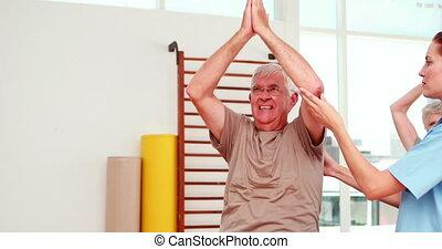 Injured senior citizen exercising with physiotherapist at the rehabilitation center
