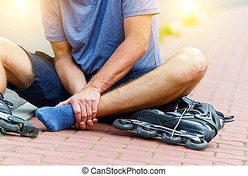 Injured skater with painful leg - Injured skater sitting and...