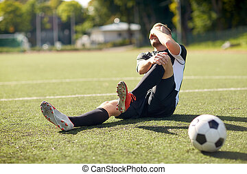 injured soccer player with ball on football field - sport,...