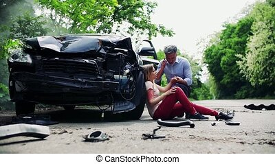 Injured woman by the car after an accident and a man making...