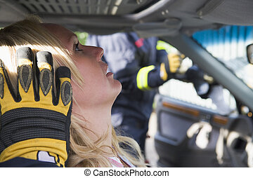 Injured woman in car with firefighter in background cutting out windshield (selective focus)