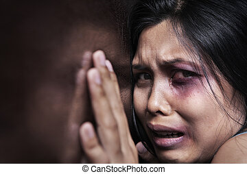 Injured woman terrified, leaning on the wooden wall. Concept for domestic violence