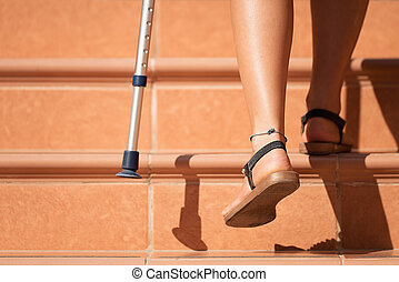 Injured woman trying to walk on crutches