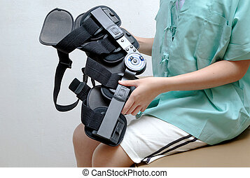 Injured woman with leg splint sitting on bed in rehab center