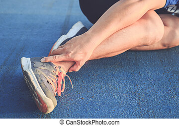 Injury from workout concept : Asian man use hands hold on his ankle while running on road in the park. Focus on ankle.