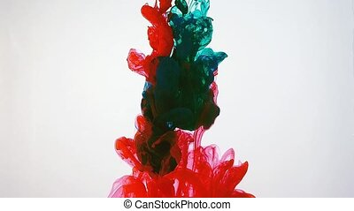 Ink moving in water, white background. Red and dark green acrylic paint swirling in water. Traces of abstract colourful clouds of ink dissolving in water ever changing shape. Shot at 60fps HD format.