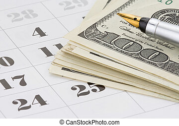 ink pen and dollar money on calendar background
