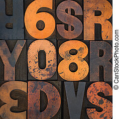 Wooden letterpress letters and numbers stained with printing ink.
