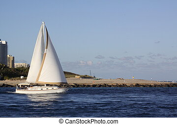 Inlet Sailing - A sailboat leaving an inlet waterway.