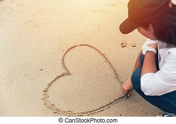 inlove girl hand drawing heart on the beach