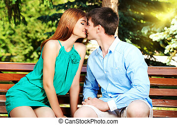 inlove kiss - Young people tenderly kissing on a park bench...