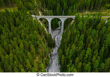 Inn River flowing in the forest in Switzerland. Aerial view from drone on an old railway bridge viaduct in the mountains