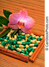 ?innamon stick, capsules, tablets, an orchid flower on the wood