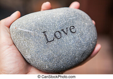 Inner balance concept: hands holding stones with the word love
