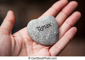 Inner balance concept: hands holding stones with the word relax