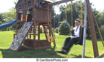 Inner Child 3 - A businessman in a suit plays on the swings