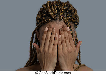 Young African American woman closing her face with two palms