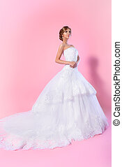 Full length portrait of a beautiful charming bride in a luxurious dress. Over pink background.