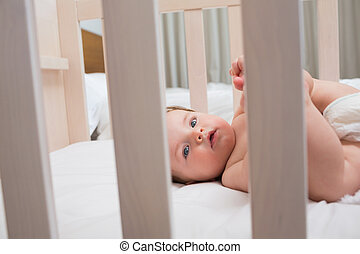 Innocent baby boy lying in crib