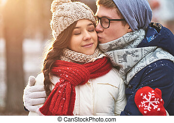 Innocent kiss - Amorous guy kissing his girlfriend on cheek...