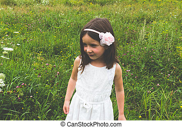 Innocent little girl in white dress outdoors in park with wild grass and flowers