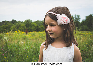 Innocent little girl outdoors in park with wild grass and flowers
