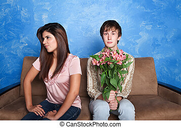 Innocent young man holds flower bouquet while his girlfriend looks away