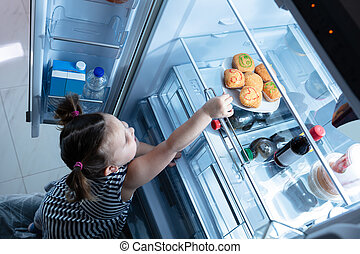 Girl Trying To Take Cupcake From The Refrigerator