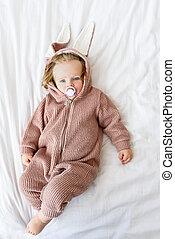 Innocent toddler in jumper on bedding
