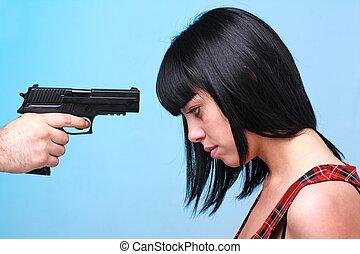 Innocent victim. Young beautiful woman and gun.