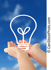 Human hands holding a stylized bulb in front of a bright blue sky.