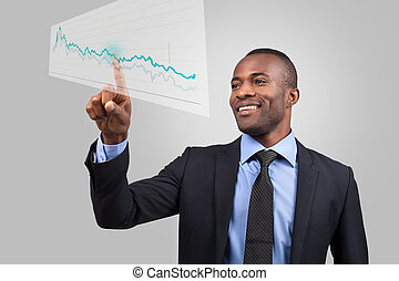 Innovative business. Cheerful young African man in formalwear pointing diagram on the transparent wipe board while standing against grey background
