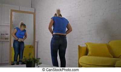 inquiet, femme, essayer, à, bouton, jean, à, effort