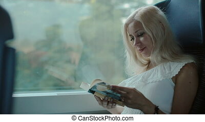 Inquisitive blonde reading a book sitting in the car of the moving train