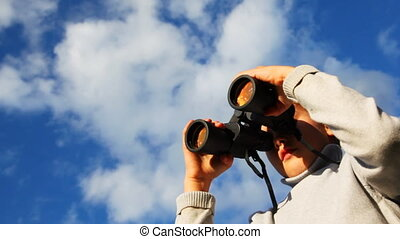 inquisitive boy looks through binoculars against sky with clouds