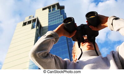 inquisitive boy looks through binoculars on background of skyscrapers, then turns