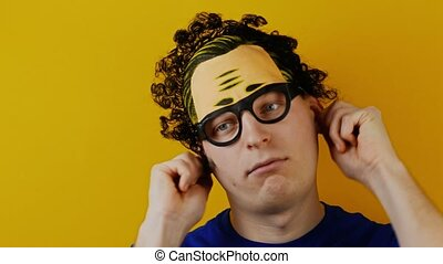 insane curly man pulls himself by the ears and shows his...