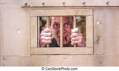 An insane prisoner laughing and making a fuss behind a jail door
