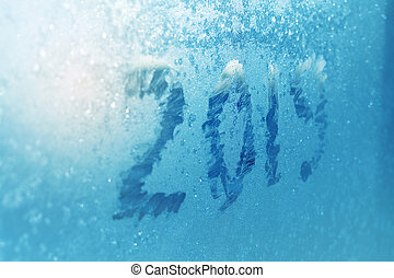 inscription 2019 on a frozen window in hoarfrost. Ice background of turquoise color. Sunlight through snowflake patterns