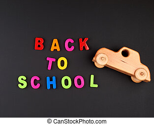 inscription back to school from multi-colored plastic letters and wooden baby car on black chalk board