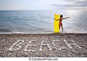 Inscription from stones BEACH at stony coast, young woman ...