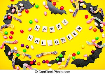 inscription from wooden blocks Happy Halloween and frame made of paper homemade bats and multicolored candies and worms from gummy