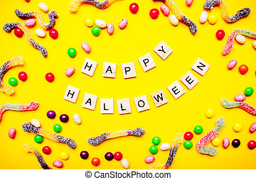 inscription from wooden blocks Happy Halloween and frame of multicolored candies and worms from gummy