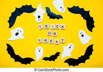inscription from wooden blocks trick or treat and frame made of paper homemade bats and paper ghosts