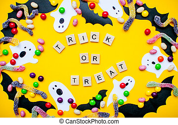 inscription from wooden blocks trick or treat and frame made of paper homemade bats and paper ghosts and multicolored candies and worms from gummy