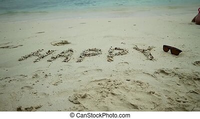 Inscription happy on sand and seascape on a background